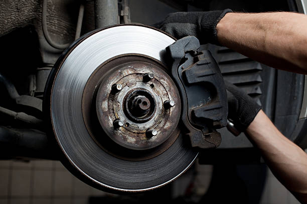 a mechanic working on a brake pad  - 剎車制 個照片及圖片檔