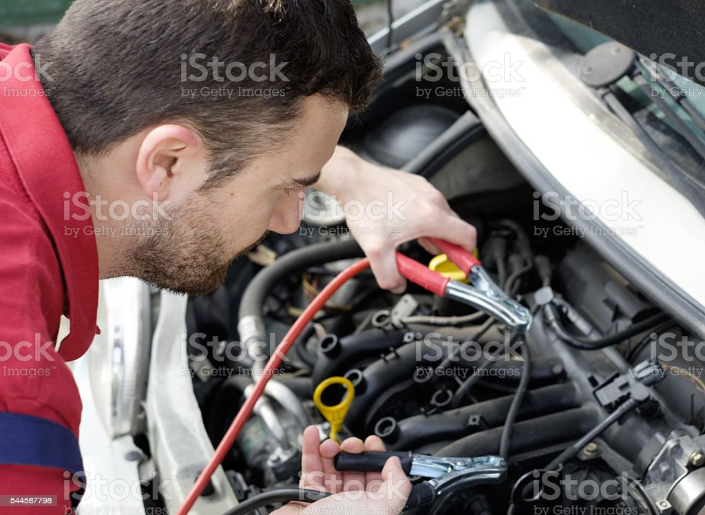 mechanic working on car engine with electricity cables stock photo