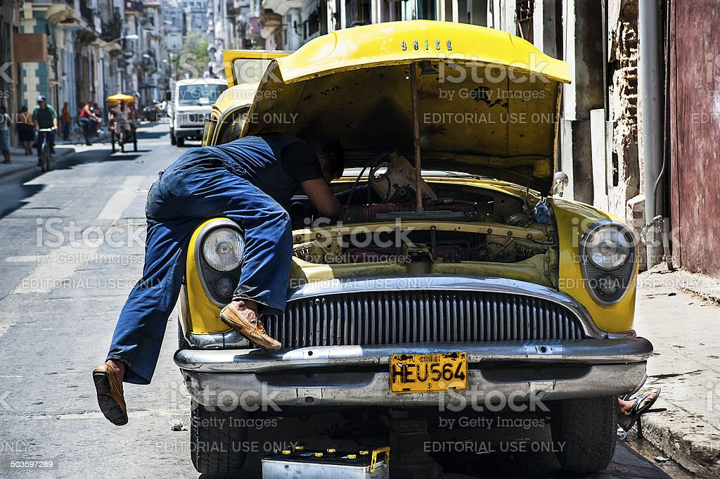 Mechanic working on his vintage Buick in Havana stree stock photo