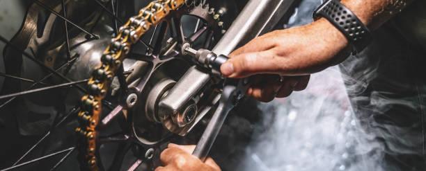 Mechanic working on Motocycle in mechanics garage. Repair service stock photo