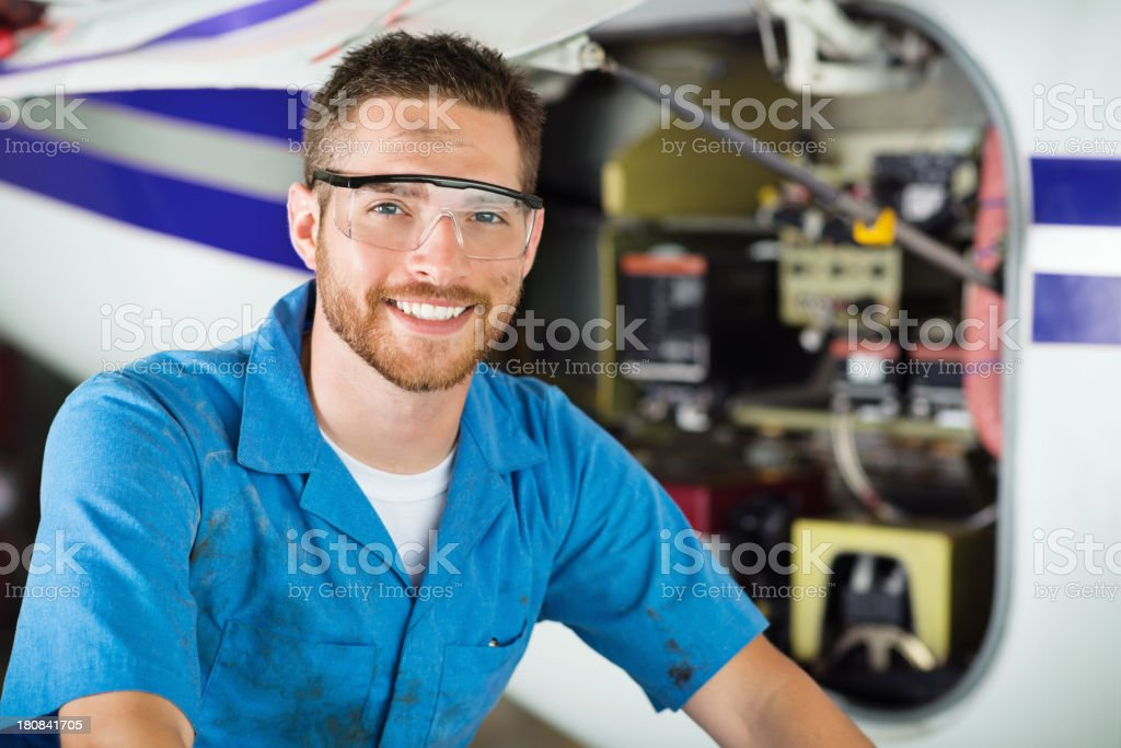 Mechanic working on private jet in airplane hangar stock photo