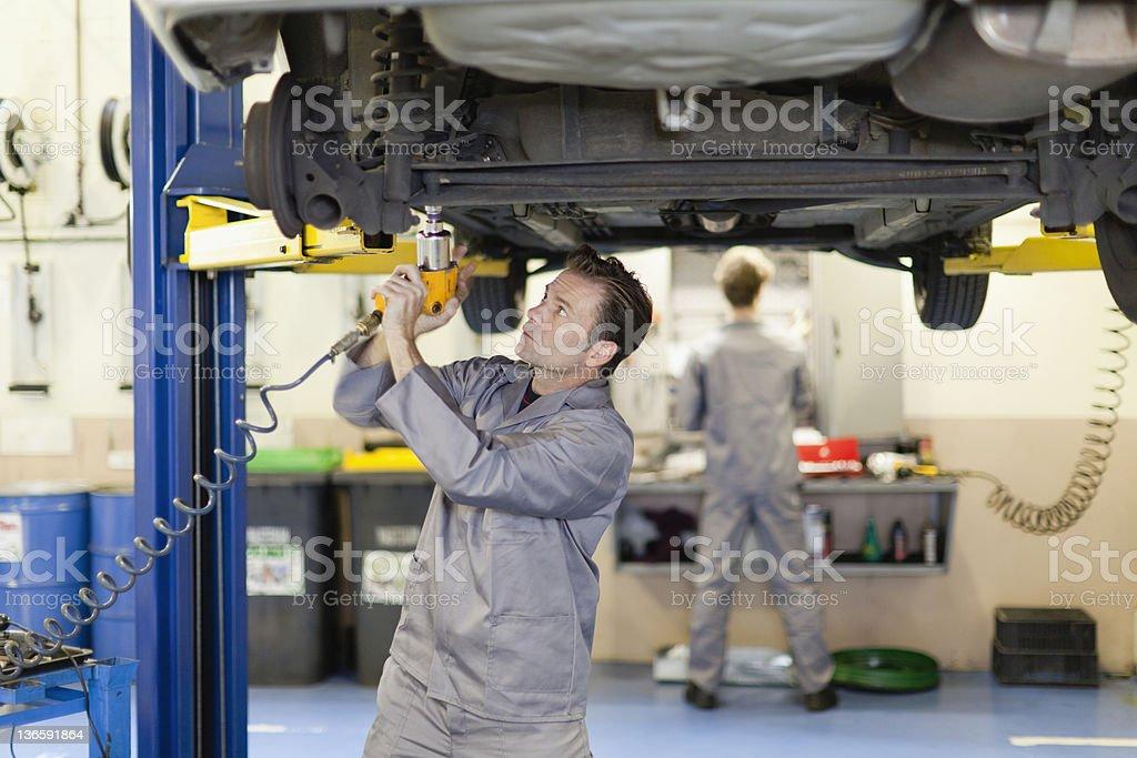 Mechanic working on underside of car stock photo