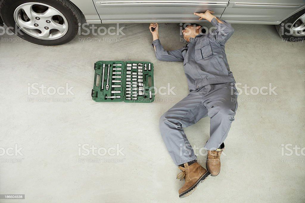 Mechanic Working on Underside of Car royalty-free stock photo