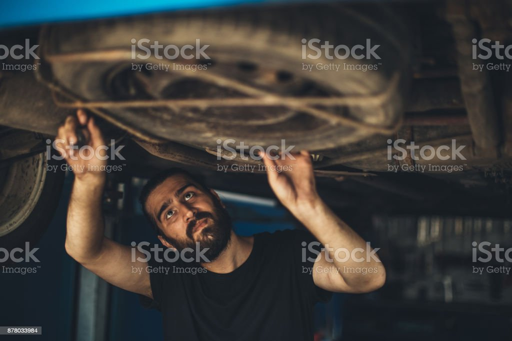 Mechanic working under a vehicle at workshop stock photo