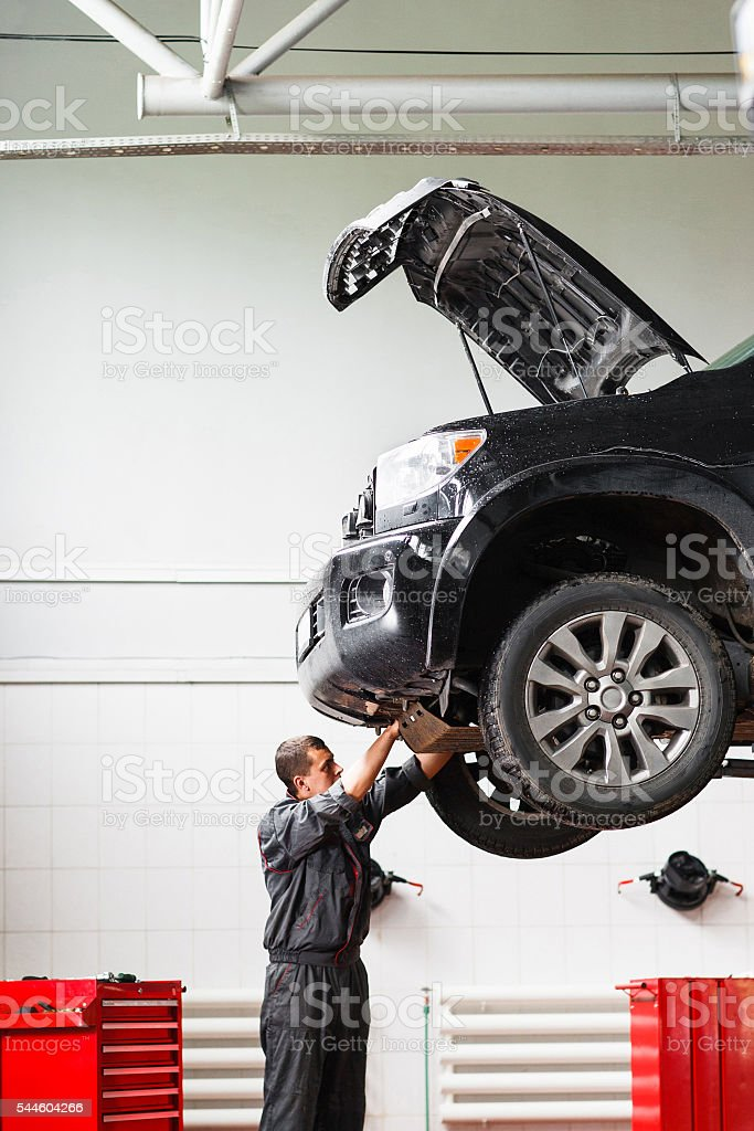 Mechanic working under car in service station stock photo