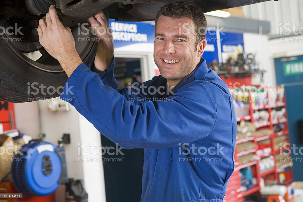 Mechanic working under car smiling royalty-free stock photo