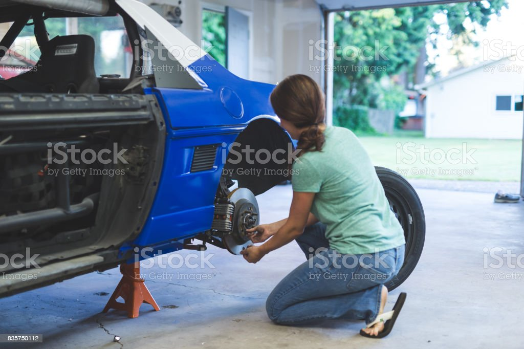 Mechanic Works On Car In Her Home Garage Stock Photo - Download