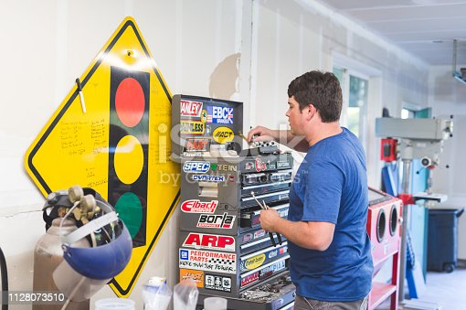 Mechanic works on car in his home garage. He is selecting tools from his sticker-covered rolling mechanic's toolchest