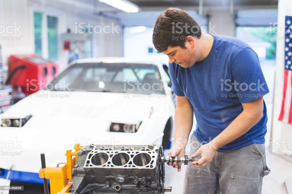 Mechanic Works On Car In His Home Garage Stock Photo - Download