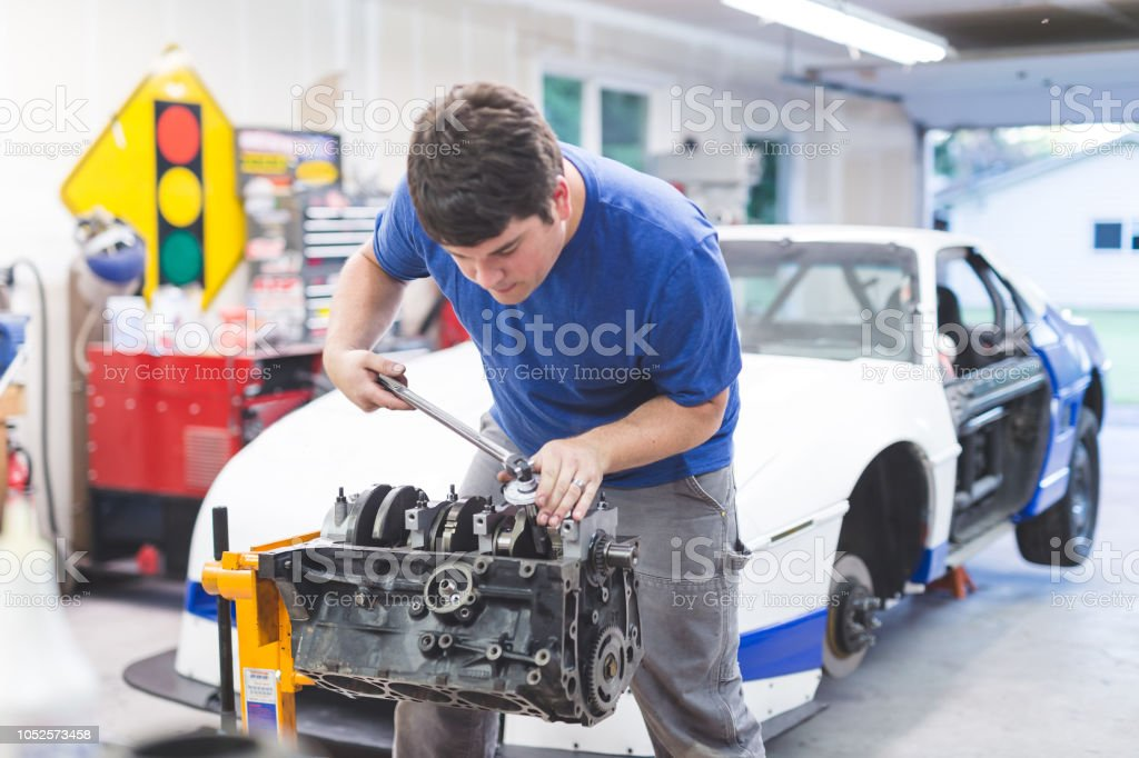 Mechanic Works On Race Car In His Home Garage Stock Photo - Download