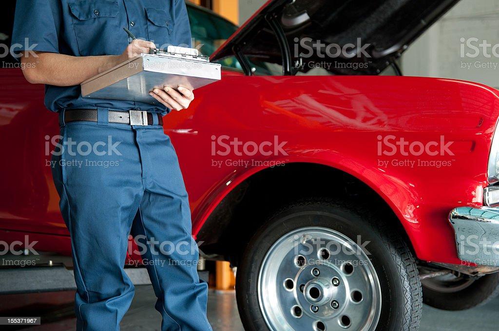 mechanic writing estimate for broken car royalty-free stock photo