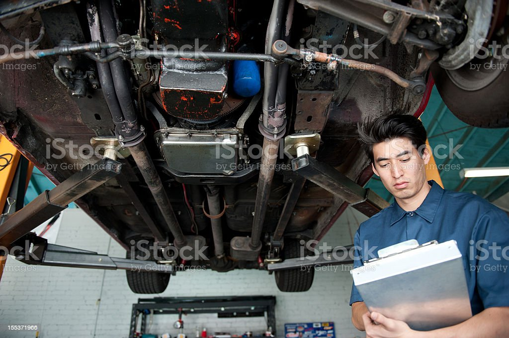 mechanic writing estimate under car royalty-free stock photo