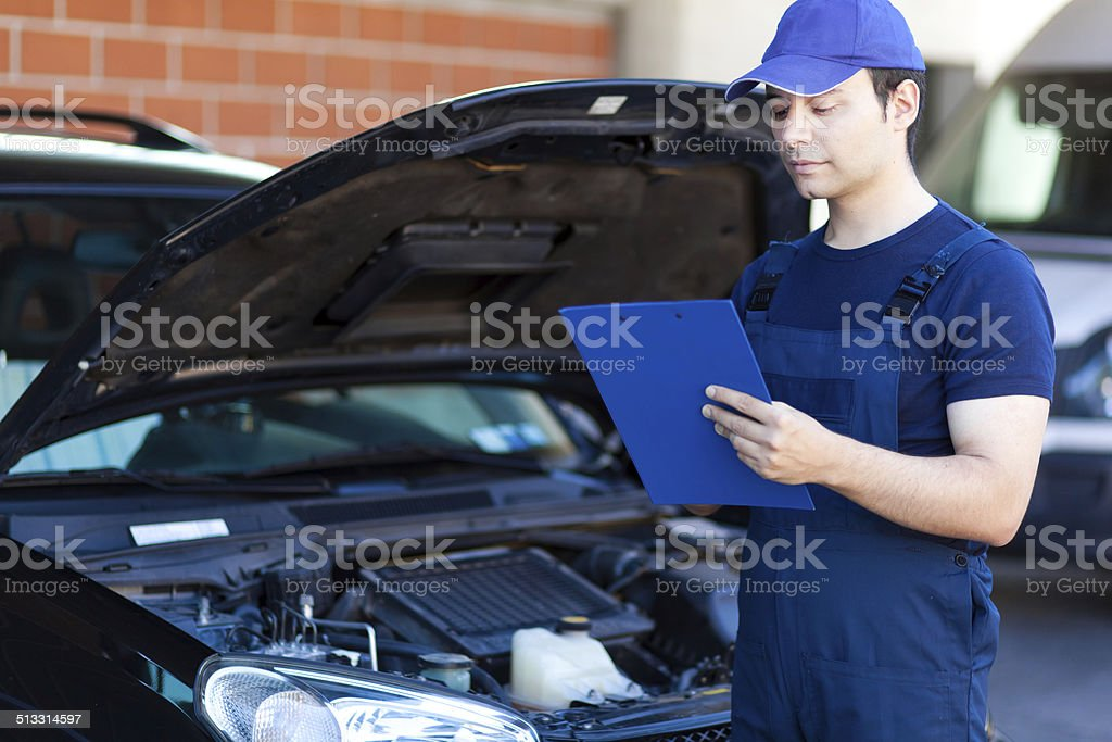 Mechanic writing on a clipboard stock photo