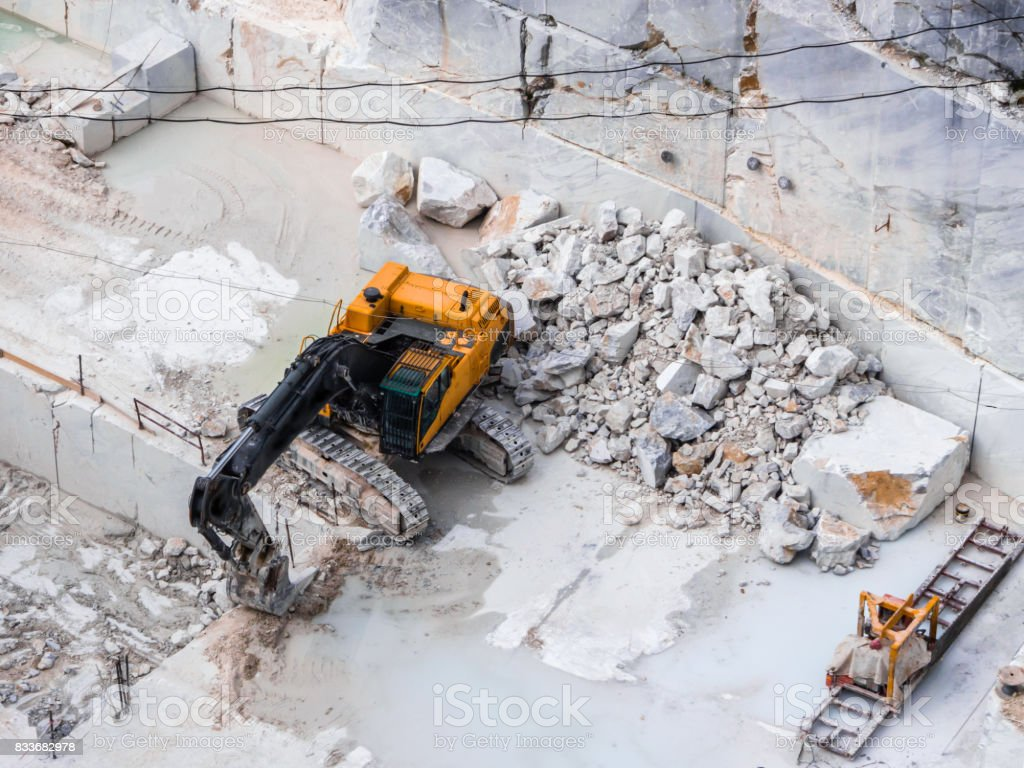Mechanical blade during excavation work in a marble quarry - foto stock
