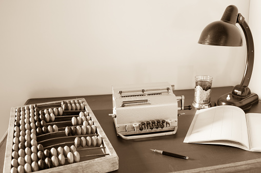 Mechanical calculator, wooden abacus, vintage table lamp on an old table. Accounting and auditing.
