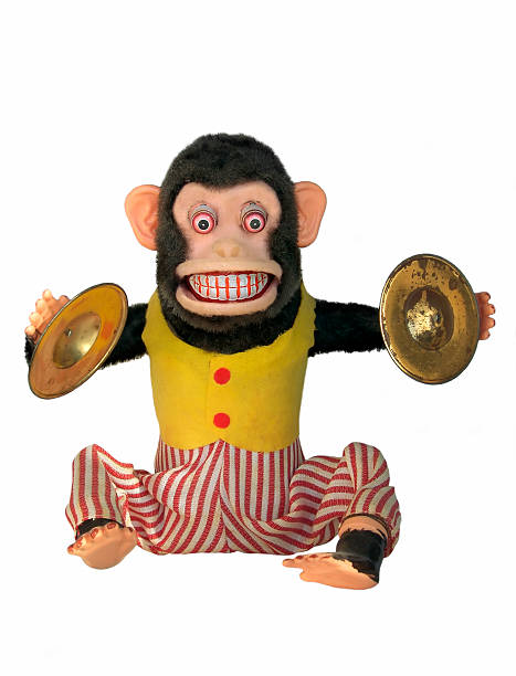 Mechanical Chimp Vintage mechanical monkey toy with cymbals showing teeth, full body isolated on white background cymbal stock pictures, royalty-free photos & images