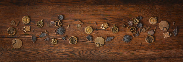 Mechanical cogwheel elements on a dark wooden surface stock photo
