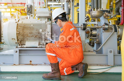 Mechanical engineer checking electric motor and centrifugal pump system at offshore oil and gas central processing platform, Oil and gas exploration and production service industry.