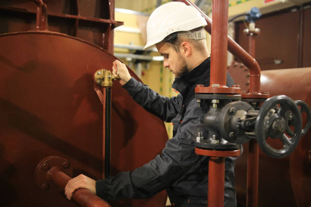 Mechanical engineer in facility oil and gas. Service work in tank of technical water. stock photo