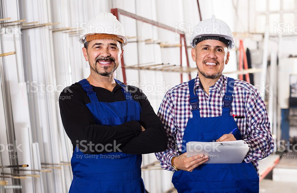 Mechanical engineer inspecting the work of labour at factory stock photo