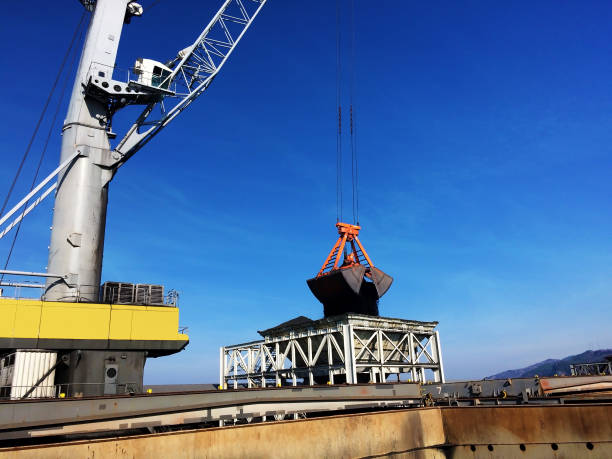 mechanical grabber loading coal by ship cranes stock photo