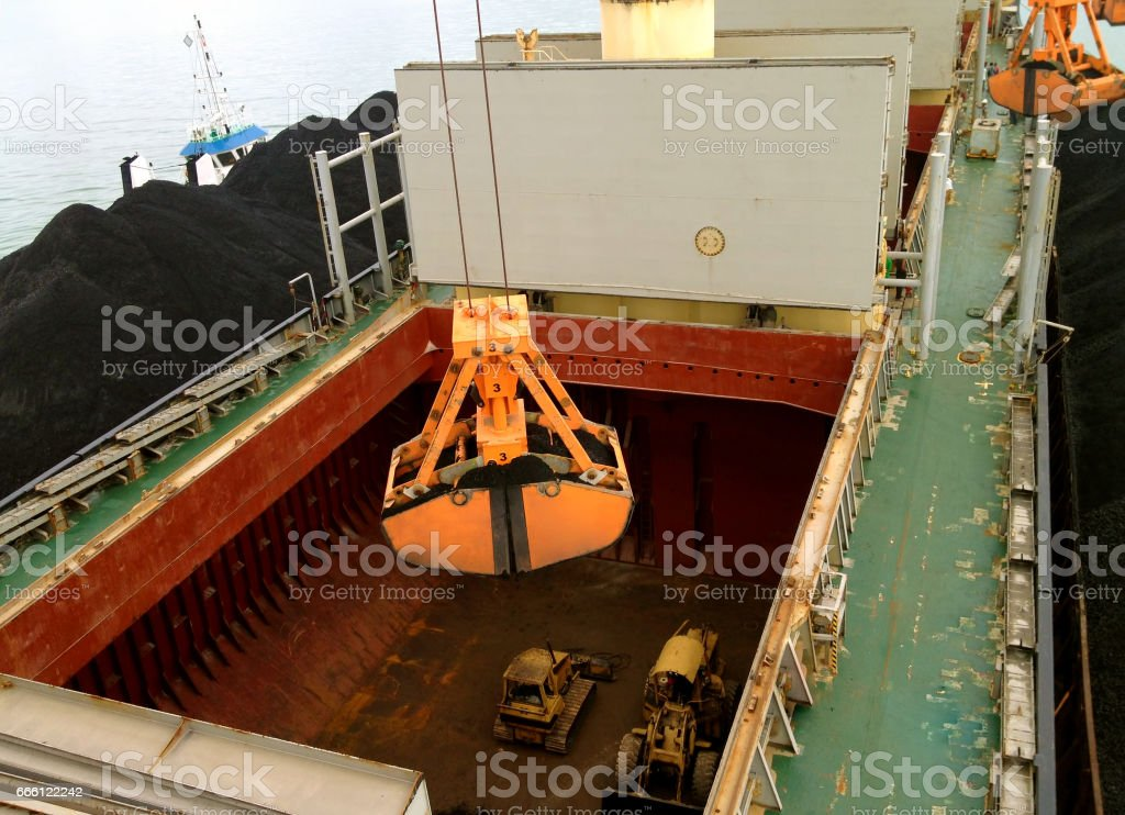 mechanical hydraulic grabbers loading coal by ship cranes stock photo