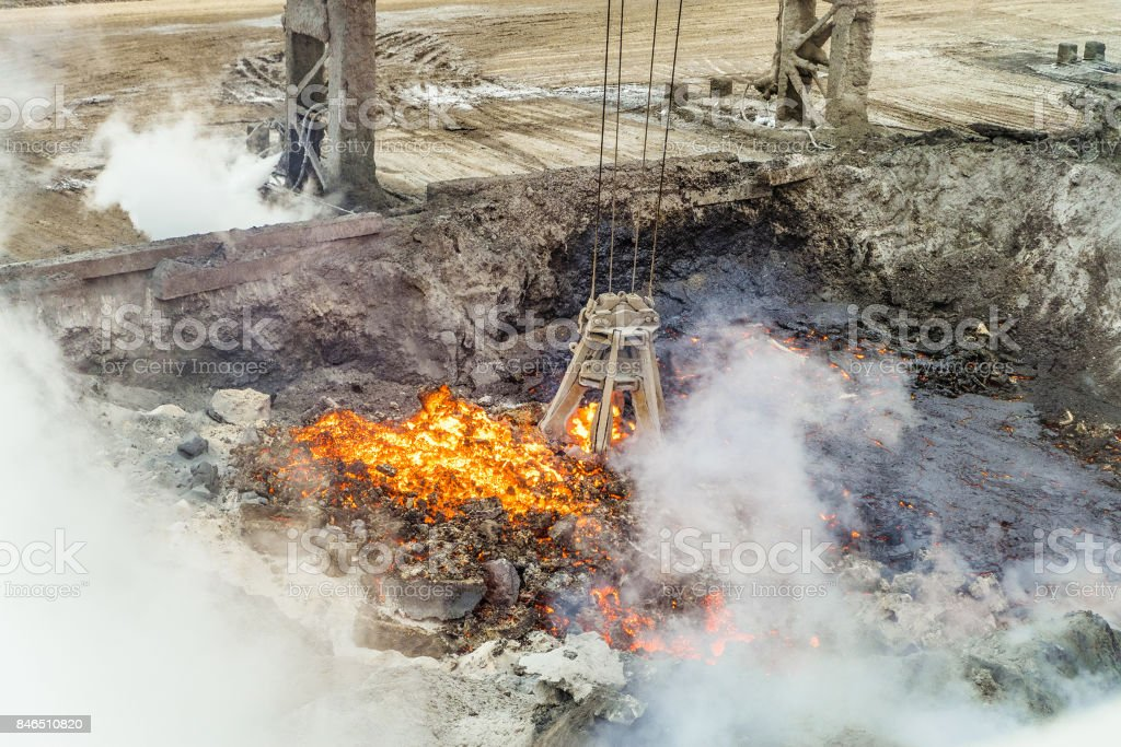 Mechanical multivalve clamshell grapple for transportation of red-hot pieces of iron from the melt on a background evaporation of molten liquid iron and slag. Metallyrgical heavy industry. stock photo