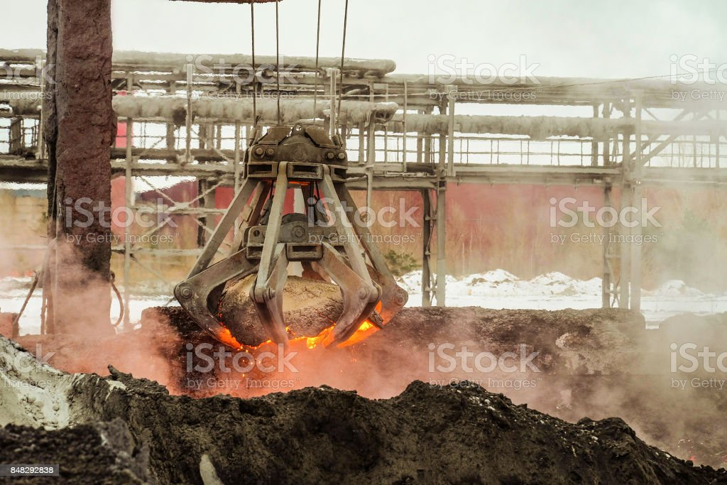 Mechanical multivalve clamshell grapple transports of red-hot piece of iron from the melt on a background evaporation of molten iron and slag. Metallyrgical heavy industry. stock photo