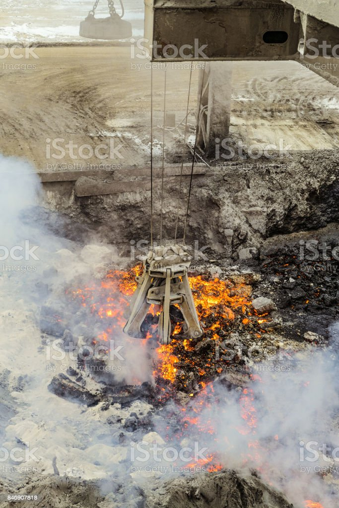 Mechanical multivalve clamshell grapple with red-hot pieces of iron from the melt on a background evaporation of molten liquid iron and slag. Heavy industry. stock photo