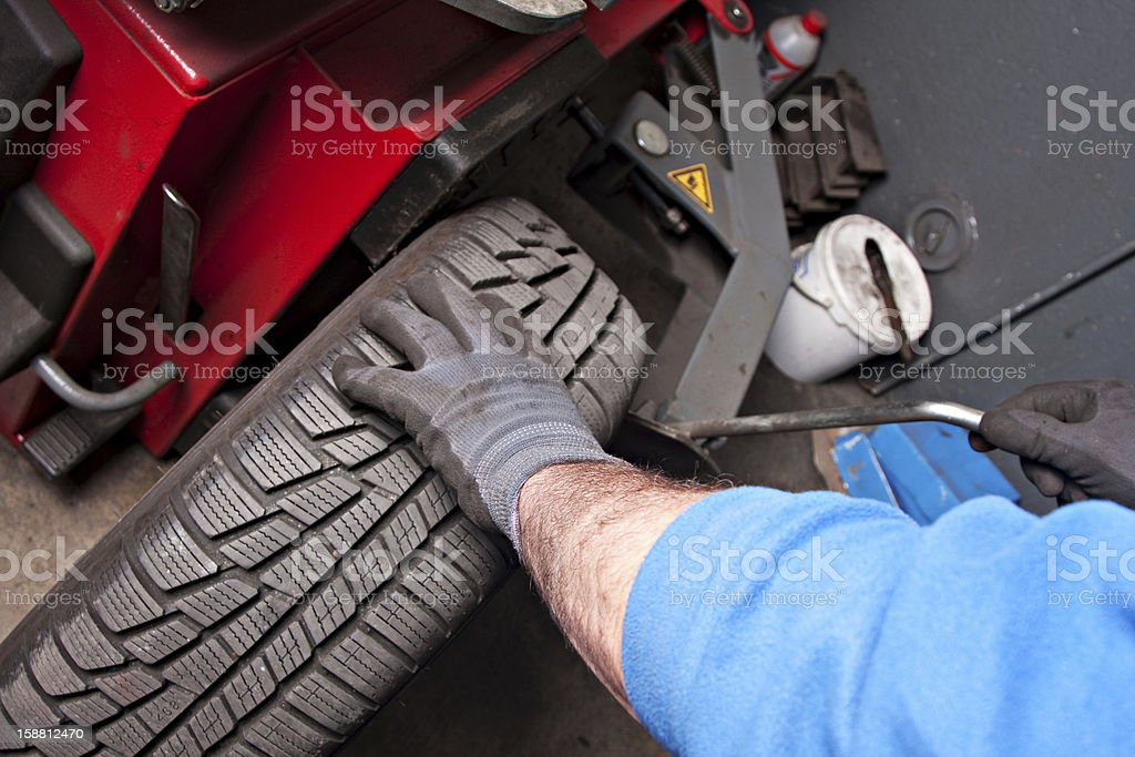 Mechanical repairs a tire in the garage. stock photo