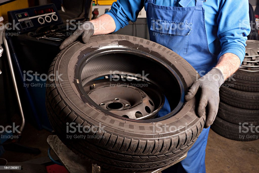 Mechanical repairs a tire in the garage - Royalty-free Adult Stock Photo