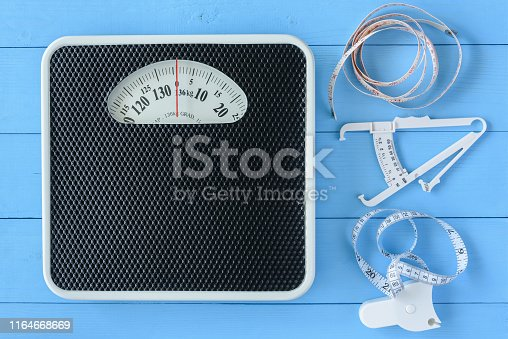 Mechanical weight scale, body mass control concept : Bathroom scale, personal accurate body fat tester / skin fold caliper measurement tool for stomach / belly and measuring tape on blue background
