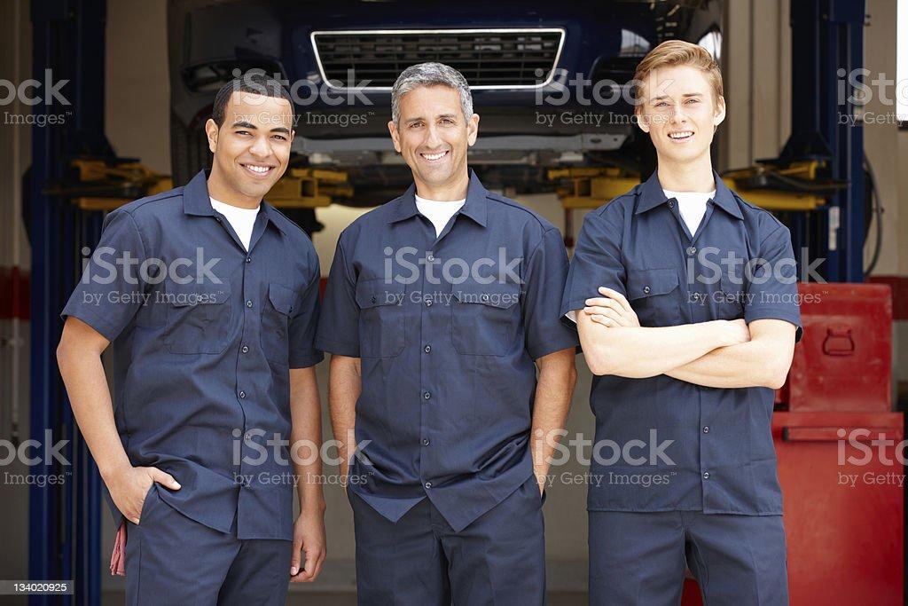 Mechanics at work Three Male mechanics at work standing in workshop 20-29 Years Stock Photo