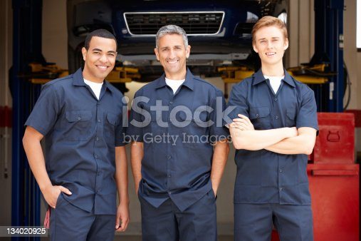 Three Male mechanics at work standing in workshop