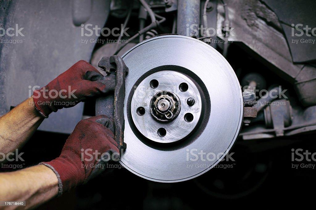 A mechanics changing a brake pad stock photo