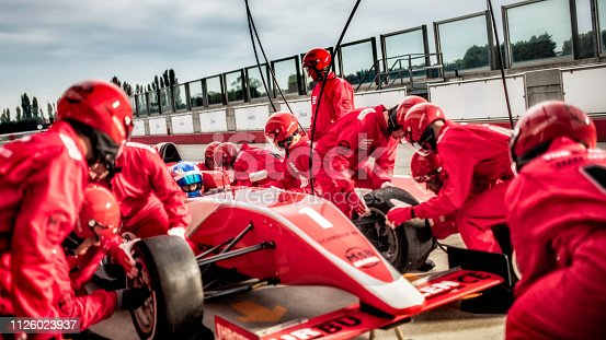 istock Mechanics changing tires on a formula during a pit stop 1126023937