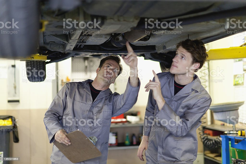 Mechanics examining underside of car stock photo