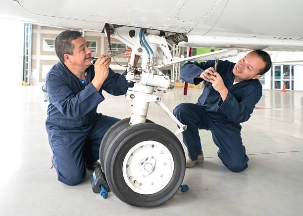 Mechanics fixing an airplane stock photo