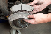 A mechanic's hands are displaying a worn to the metal brake pad (lower) and a new pad (upper). The background is a full size SUV brake rotor supported by a jack stand.