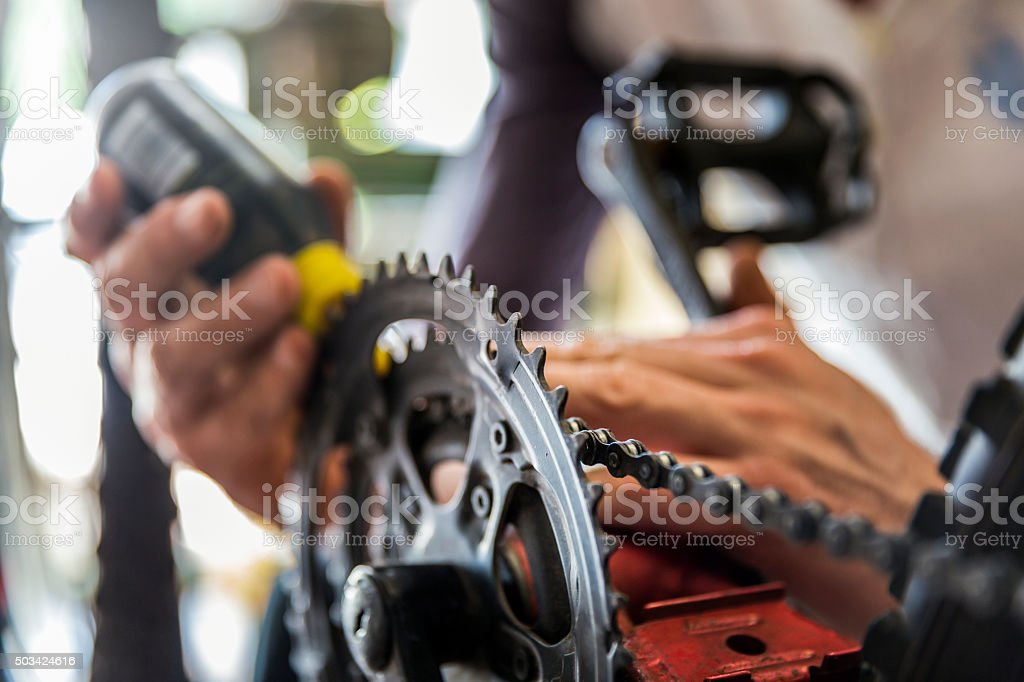 Mechanic's hands oiling bicycle chain stock photo