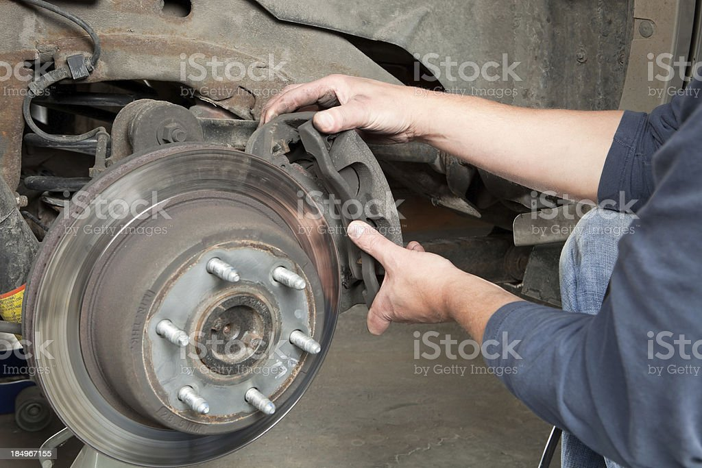 Mechanic's Hands Remove a Disk Brake Caliper from Rotor stock photo