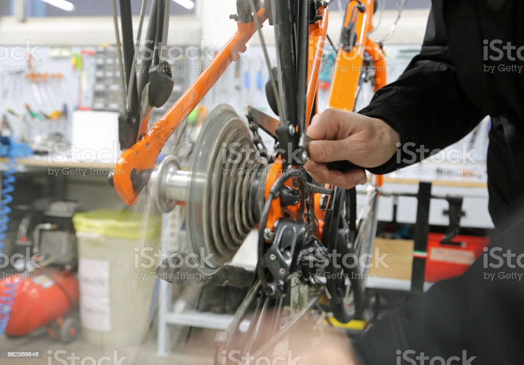 mechanics while repairing the transmissione gear of a bicycle stock photo