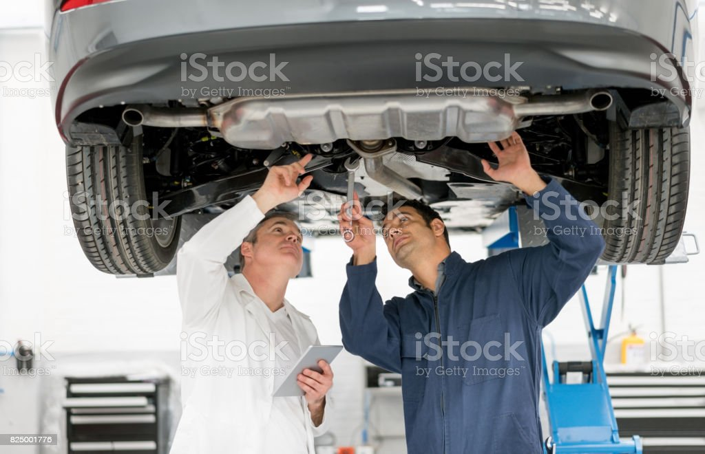 Mechanics working at an auto repair shop checking the chassis of a car stock photo
