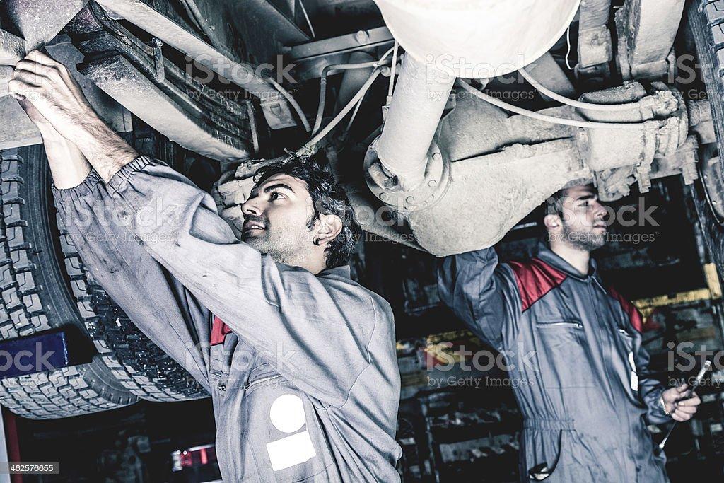 Mechanics working below a truck stock photo