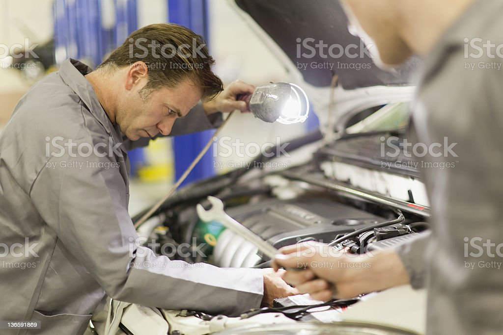 Mechanics working on car engine stock photo