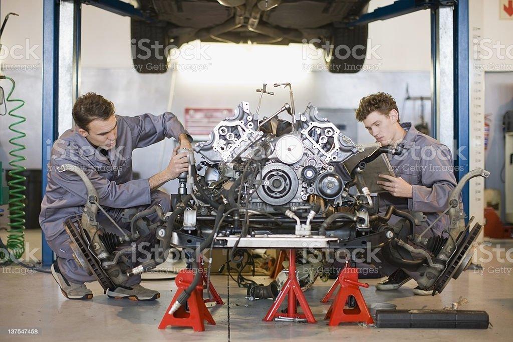 Mechanics working on car engine stock photo