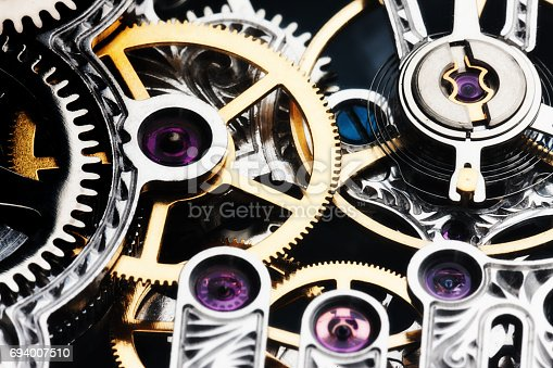A close up of the inner workings of a luxury watch with a jewelled mechanism.