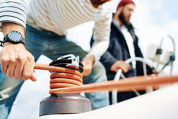 Mechanism of sailing Male hands rolling rope around bollard rigging stock pictures, royalty-free photos & images