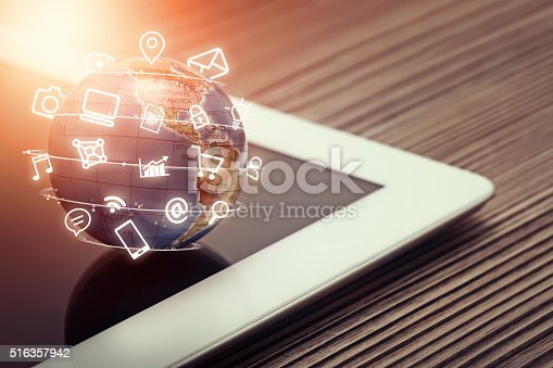 istock media app icons flying around globe on tablet computer 516357942