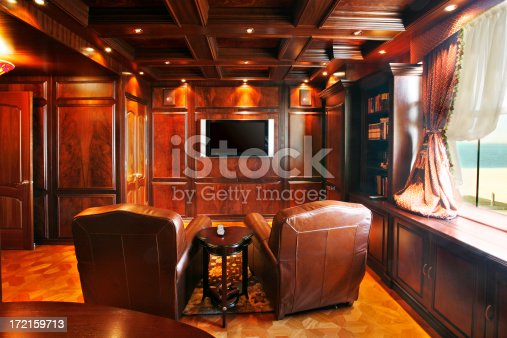 A richly paneled media room with screen and seats.